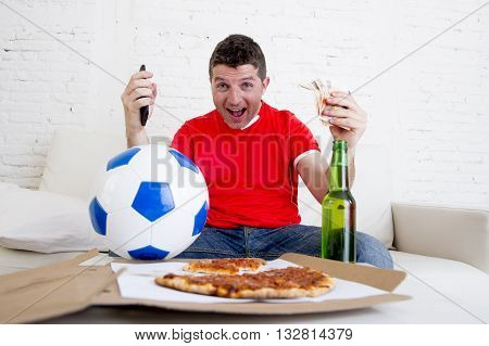 young man holding mobile phone and money in his hands watching football game on television happy and excited winning on line bet in internet gambling concept