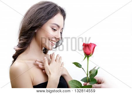 Beautiful girl receives one red rose. She is surprised, looking at the flowers and smiling. Men's hand holding one rose. Girl is white with bushy brown hair. Isolated on white background.