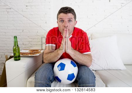 young man watching football game on television nervous and excited suffering stress praying god for goal on sofa couch at home with ball beer bottle and pizza looking crazy anxious