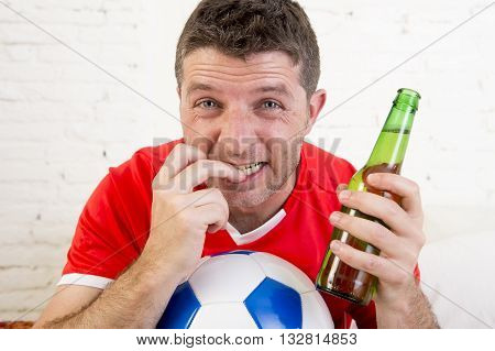 close up face of young fan man watching football game on television wearing team jersey suffering nervous and stress biting fingernails on sofa couch at home holding soccer ball and with beer