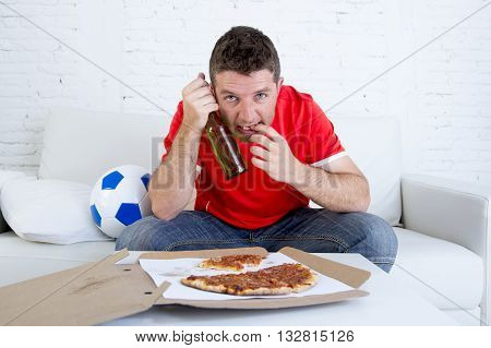 young fan man watching football game on television wearing team jersey suffering nervous and stress on sofa couch at home holding beer bottle biting fingernails stressed