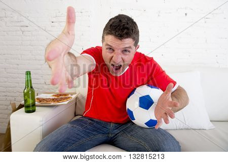 young supporter man with ball and beer bottle watching football game on television sitting at home couch in stress dejected and disappointed for failure shouting and complaining