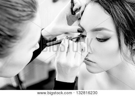 Stylist makes professional eyes makeup. Beautiful model. Grayscale.