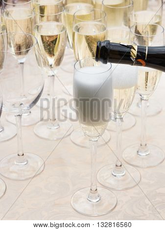sparkling champagne is poured from a bottle in a dark transparent glass tall glasses at corporate