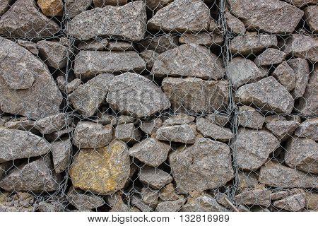 wall of granite stones. Reinforced mesh netting.