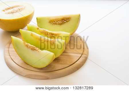 Left in front on the round wooden kitchen board lying melon slices behind half of melon and slices right empty place for text on the white background. Slices of melon. Horizontal.