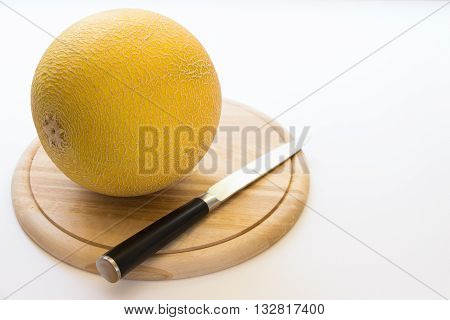 Left in front on the round wooden kitchen board lying one melon near knife right empty place for text on the white background. Melon and knife. Horizontal.