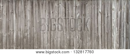 Long gray wooden fence consisting of old weathered unpainted boards