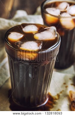 Cold black coffee with ice cubes in glass
