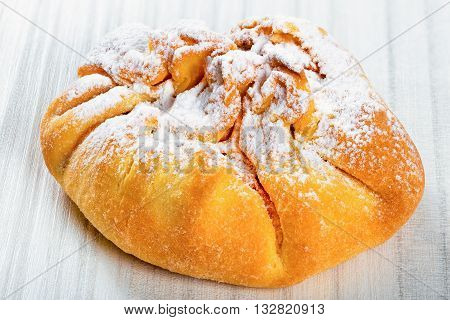 Coconut puff pastry on a white wooden table sprinkled with icing sugar close up