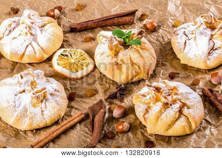 Сoconut puff pastries on parchment paper sprinkled with sugar icing close up