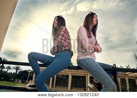 two beautiful offended girls photographed in park on walk