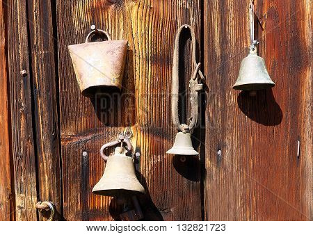 antique old style retro object assemblage on a wooden wall. rustic stile. Old shepherd's bells