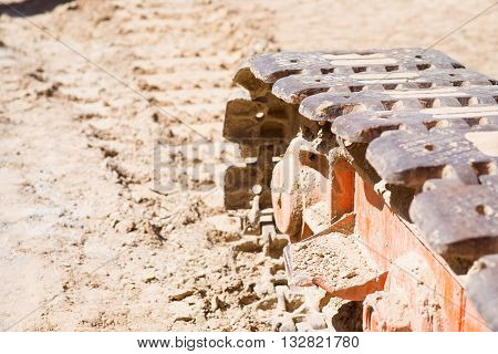 Track of a machine.  A part of a track of a crane being in sand while being used in construction works, picture may be used as a background