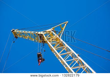 Crane operations.  A part of a crane being used in construction works standing against blue sky, picture may be used as a background