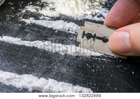Man Is Making Lines Of Cocaine White Powder For Snorting.