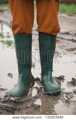 woman in rubber boots standing in a puddle after a summer rain in the village