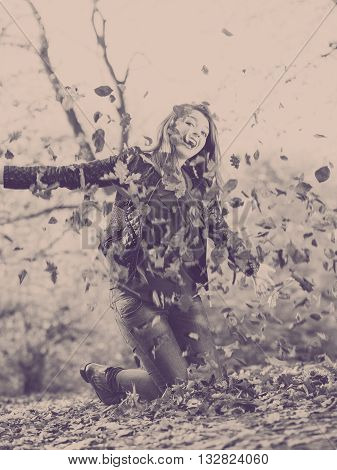 Autumn people nature concept. Young lady is super happy autumn has just come. Female is playing with leaves in park.