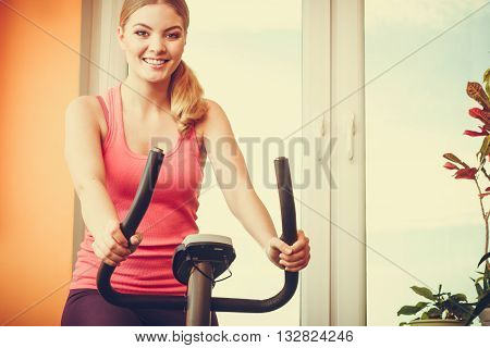 Active human working out on exercise bike stationary bicycle. Sporty person training at home. Fitness and weight loss concept.