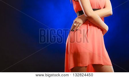 Party clothing evening fashion concept - attractive fashion woman mixed race girl in orange elegant dress part of body hips dark blue background