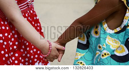Diversity:  Caucasian and African - American little girls holding hands