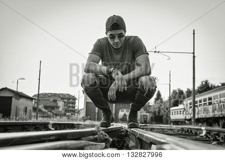 Attractive young man sitting on railroad, wearing grey t-shirt and jeans, looking away