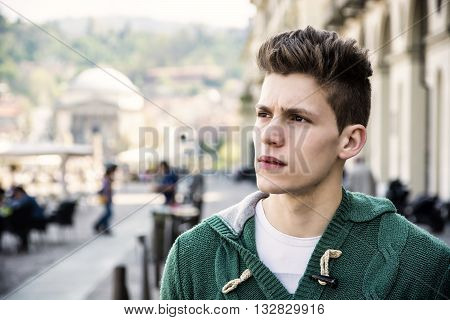 Headshot of handsome young man in city street, looking at camera