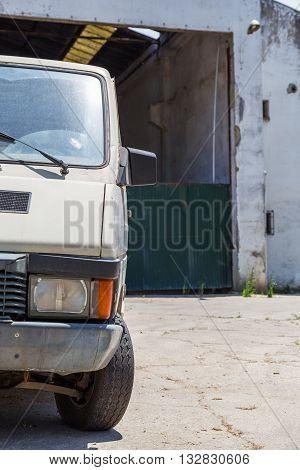 a abadoned work car near deserted storage