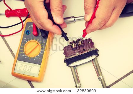 Mechanical engineering domestic industrial concept. Heater tested by mechanic. Engineer checking heating part washing machine.