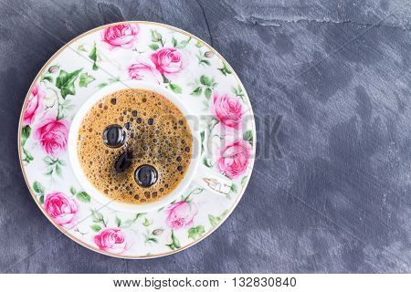 Cup of strong black Turkish coffee in a pretty porcelain cup with pink roses viewed from above on a slate background with copy space