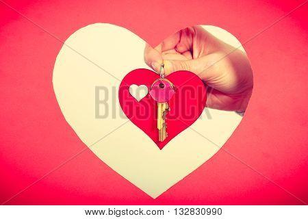 Female Hand Holds Little Heart With Keys.