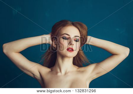 Close-up portrait beautiful girl on a blue background. Woman showing her armpits