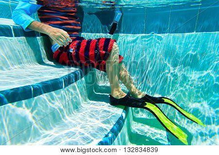 Underwater kids legs in fins in swimming pool, active kids