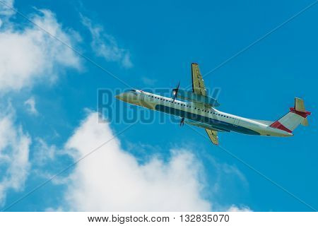 Turboprop Jet Airplane Traveling. Airplane on the Cloudy Blue Sky.