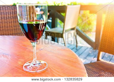 Glass of red wine on the table in restaurant at summer.