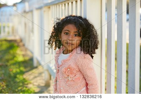 Happy toddler kid girl portrait in a park fence latin ethnicity