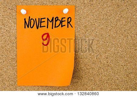 9 November Written On Orange Paper Note