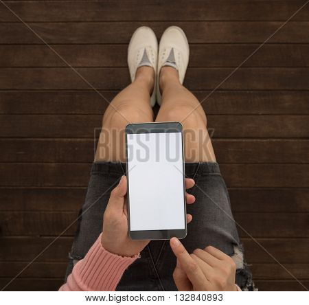 Close up of a young women using mobile smart phone. Blank screen for your advertising. View from above.