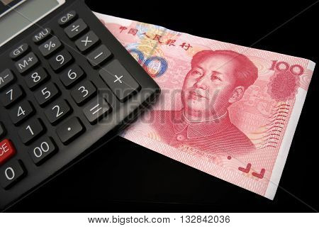 Renminbi bank note juxtaposed against a calculator