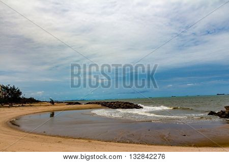 The sea bend at the beach with the blue sky.