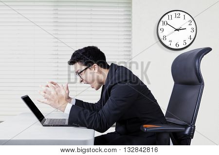 Portrait of angry caucasian businessman screaming at laptop on the desk shot in the office