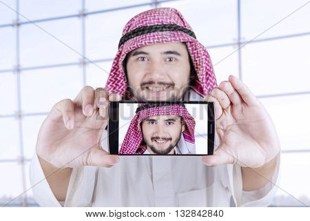 Portrait of Arabian person using a mobile phone to take selfie photo in the airport
