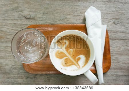 Set of hot coffee with streamed milk and a light layer of foam on wooden tray served with ice water and a piece of napkin