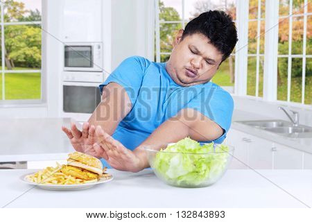Overweight person refuses to eat a plate of fast food on the table in the kitchen at home