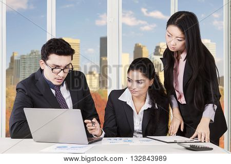 Image of middle eastern businessman speaking with indian and chinese businesswomen at the workplace