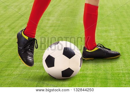 Closeup of soccer player dribbles the ball on the field