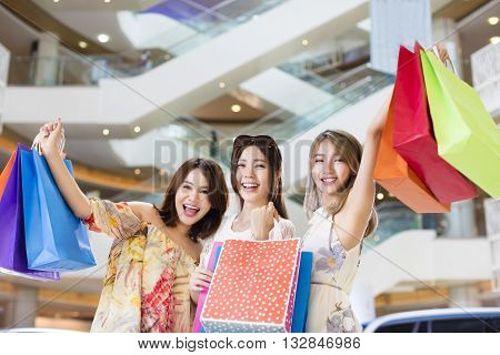 happy Women group Carrying Shopping Bags in mall