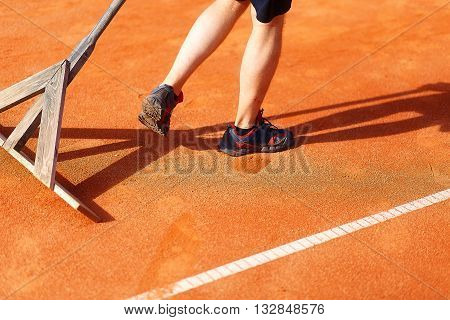Man fixes the lines on tennis courts