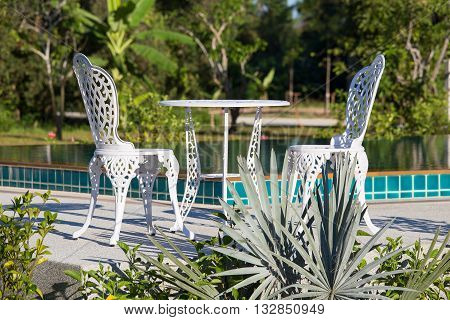 Table and two chairs with swimming pool in tropical garden. Thailand