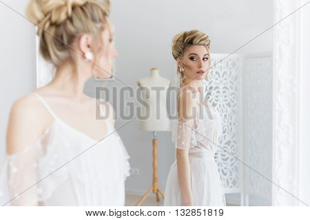 beautiful cute sweet young girl in a light dress beautiful boudoir with bright makeup smokey eyes with a beautiful evening hairstyle and jewelry handmade